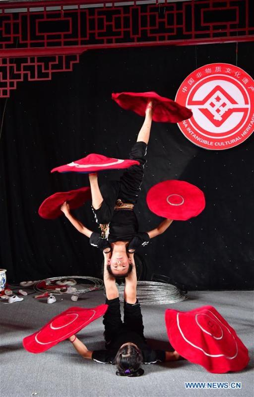 Trainees practice at an acrobatics school in Dongbeizhuang Village of Puyang, central China\'s Henan Province, July 11, 2018. In Dongbeizhuang Village, an acrobatics school enrols some 40 trainees aged between five and 15 who are faced with financial difficulties. The school offers both skills trainings and academic lessons but charges no tuition fees, preparing the trainees to join larger troupes with greater opportunities. (Xinhua/Feng Dapeng)