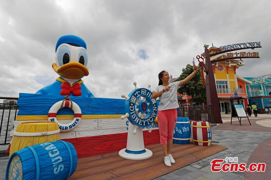 A visitor takes a selfie with an 11-meter-tall rubber Donald Duck in Wishing Star Lake at the Shanghai Disney Resort, July 12, 2018. (Photo/China News Service)