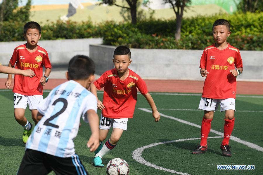 Students of a local primary school compete in a friendly soccer match during summer vacation in Renhuai, southwest China\'s Guizhou Province, July 12, 2018. (Xinhua/Chen Yong)