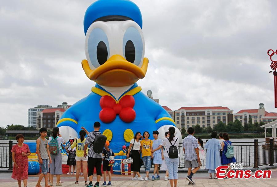 Visitors pose for photos with an 11-meter-tall Donald Duck in Wishing Star Lake at the Shanghai Disney Resort, July 12, 2018. (Photo/China News Service)