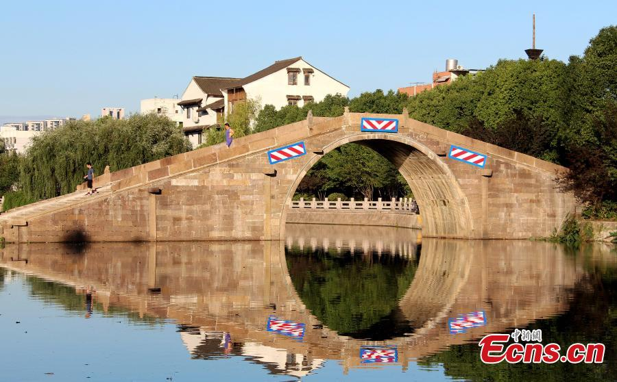 A view of the newly opened Huanxi Yongning Bridge in Hangzhou, Zhejiang Province, July 13, 2018. A part of the ancient stone arch bridge, built in 1770, collapsed due to heavy rain on July 6 and reconstruction has now been completed. (Photo: China News Service/Zhu Zi)