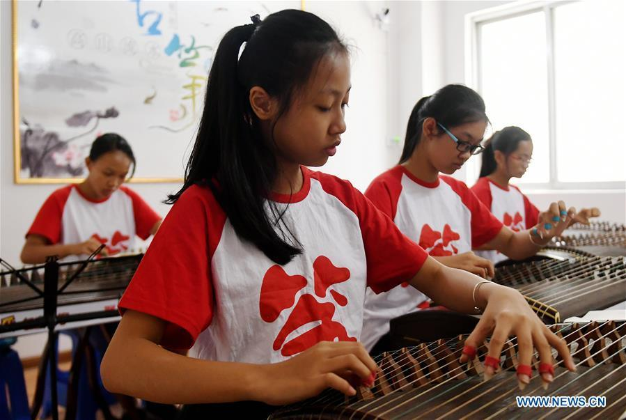 Students learn playing zither during a class in Qinzhou City, south China\'s Guangxi Zhuang Autonomous Region, July 12, 2018. Students learn new skills during their summer vacation. (Xinhua/Zhang Ailin)