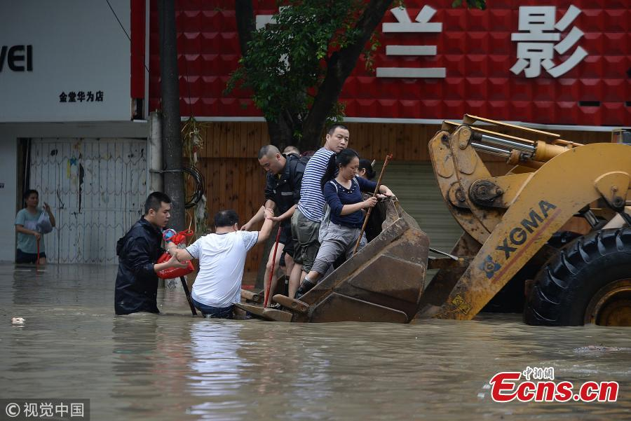 A bulldozer transports people on a flooded street in Jintang County, Southwest China's Sichuan Province, July 12, 2018, after heavy rain. (Photo/VCG)