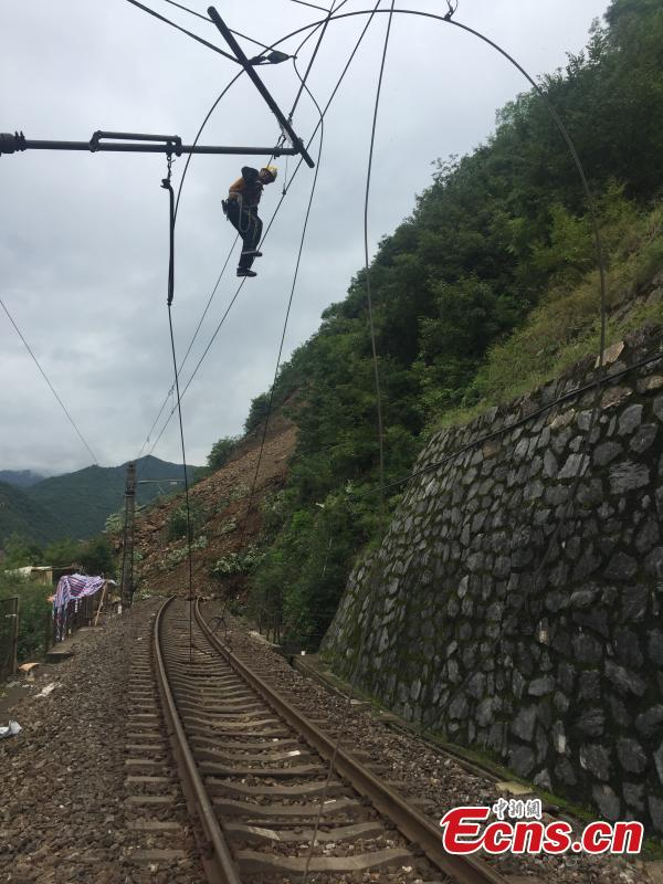 Rescuers work to clean up a landslide that cut off the Baoji-Chengdu railway line in Lueyang County, Northwest China's Gansu Province, July 13, 2018 after continuous heavy rain. Local railway authorities have mobilized thousands of people to resume train operations. (Photo provided to China News Service)