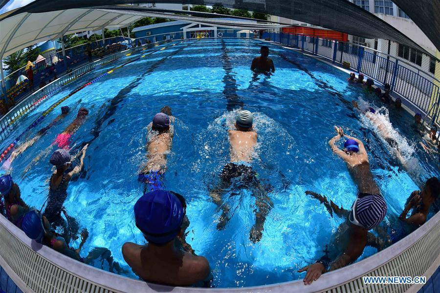 Students of a local primary school attend a swimming class during summer vacation in Qionghai, south China\'s Hainan Province, July 12, 2018. (Xinhua/Meng Zhongde)