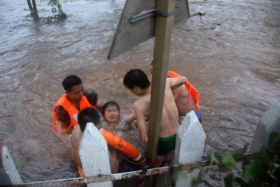 A woman is rescued from flood waters and carried to safety in Huairou district, Beijing, on July 16, 2018. (Photo provided to chinadaily.com.cn)