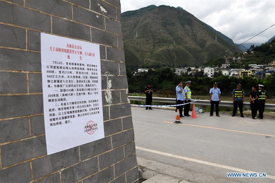 Road access to flood-hit areas is blocked due to traffic control in Nanyu Town of Zhouqu County, northwest China\'s Gansu Province, July 15, 2018. Emergency relief supplies have been sent to severely flooded areas in Zhouqu County and rescue work has been carried out here. Heavy rainstorms triggered a landslide Thursday in Zhouqu County, but no casualties have been reported. (Xinhua/Fan Peishen)
