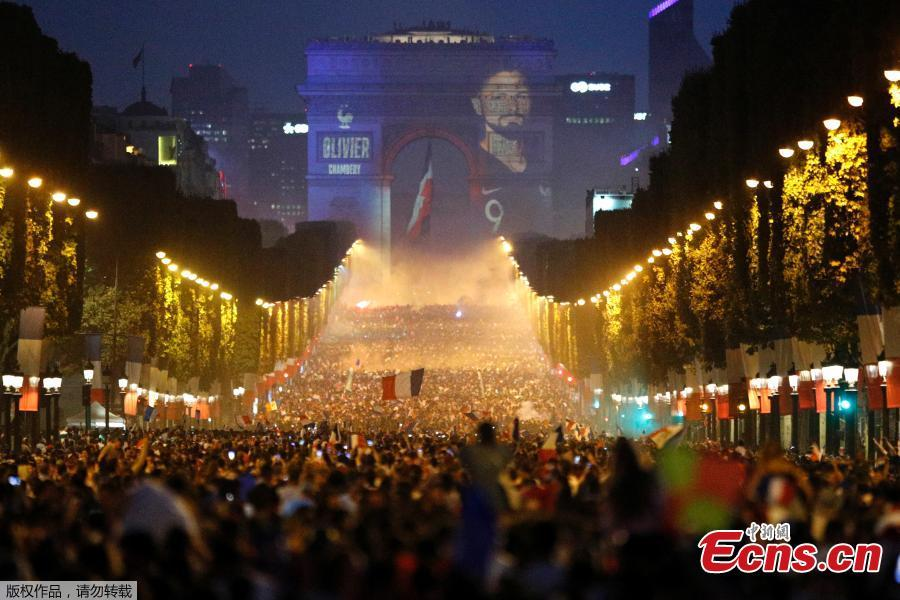A giant picture of France\'s Antoine Griezmann is seen on the Arc de Triomphe as France fans celebrate on the Champs-Elysees Avenue after France won the Soccer World Cup final, July 15, 2018. (Photo/Agencies)