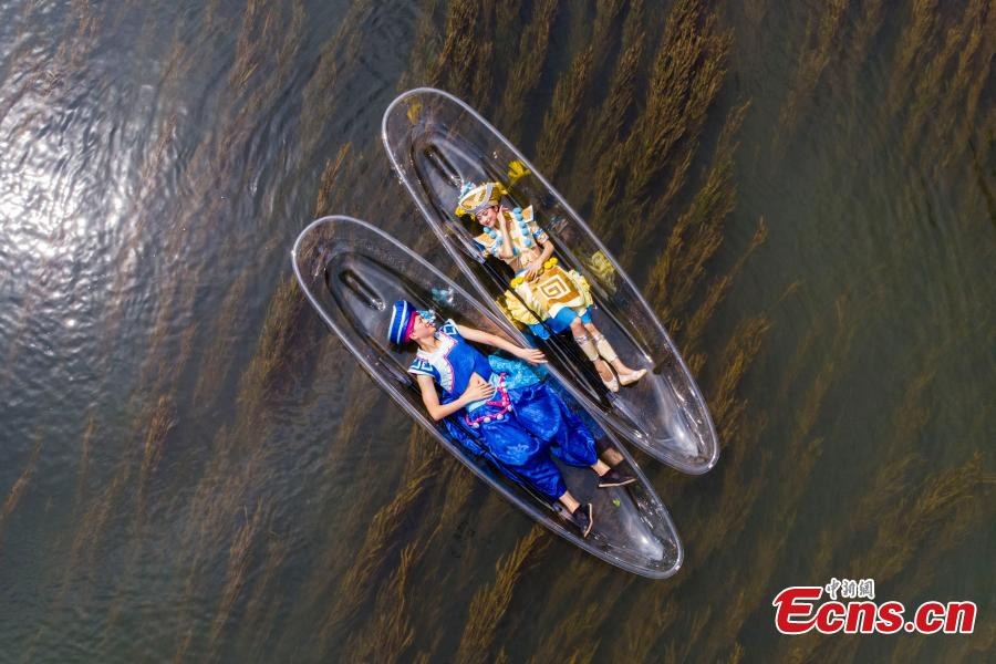 Performers lie on transparent boats as they rehearse for a show on the Lijiang River in Guilin City, South China's Guangxi Zhuang Autonomous Region, July 15, 2018. (Photo: China News Service/Chen Chao)