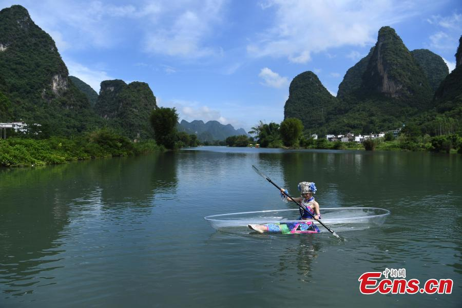 A performer rows a transparent boat in a rehearsal for a show on the Lijiang River in Guilin City, South China's Guangxi Zhuang Autonomous Region, July 15, 2018. (Photo: China News Service/Chen Chao)