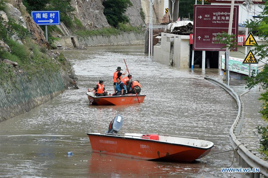 Rescuers work in Nanyu Town of Zhouqu County, northwest China\'s Gansu Province, July 15, 2018. Emergency relief supplies have been sent to severely flooded areas in Zhouqu County and rescue work has been carried out here. Heavy rainstorms triggered a landslide Thursday in Zhouqu County, but no casualties have been reported. (Xinhua/Fan Peishen)