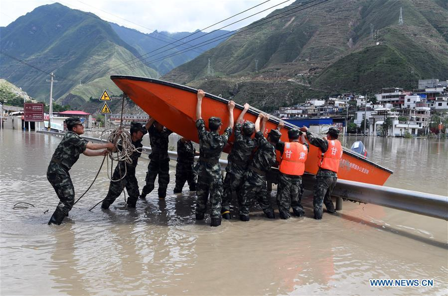 Soldiers carry a rescue boat in Nanyu Town of Zhouqu County, northwest China\'s Gansu Province, July 15, 2018. Emergency relief supplies have been sent to severely flooded areas in Zhouqu County and rescue work has been carried out here. Heavy rainstorms triggered a landslide Thursday in Zhouqu County, but no casualties have been reported. (Xinhua/Fan Peishen)