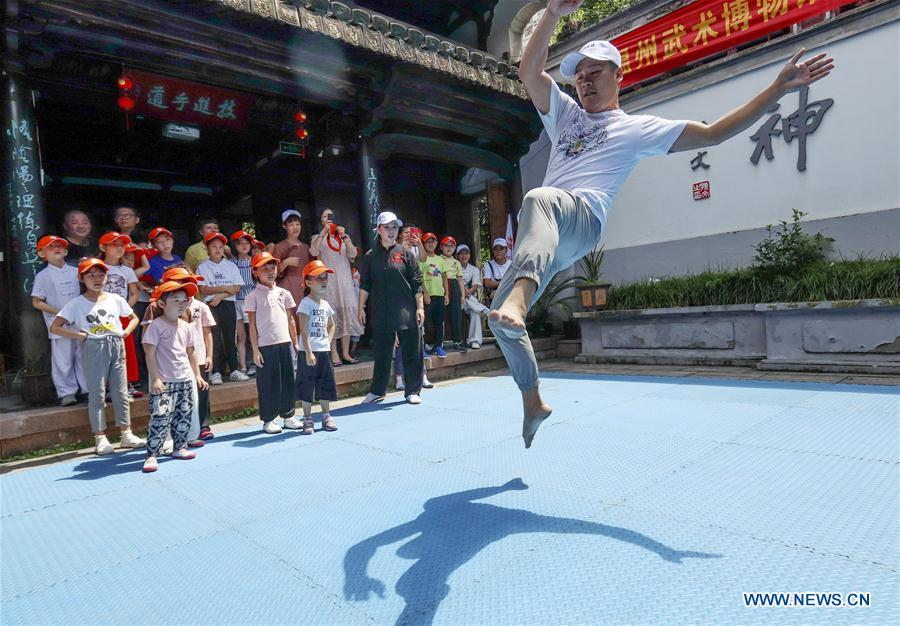 A martial arts instructor demonstrates actions for children at Wenzhou Wushu Museum in Wenzhou, east China\'s Zhejiang Province, July 14, 2018. More than 120 children visited the museum on Sunday to learn about martial arts. (Xinhua/Su Qiaojiang)