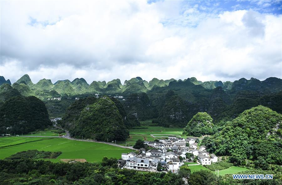 Photo taken on July 15, 2018 shows a village embraced by karst hills within the Wanfenglin scenic area in Xingyi, southwest China\'s Guizhou Province. (Xinhua/Tao Liang)