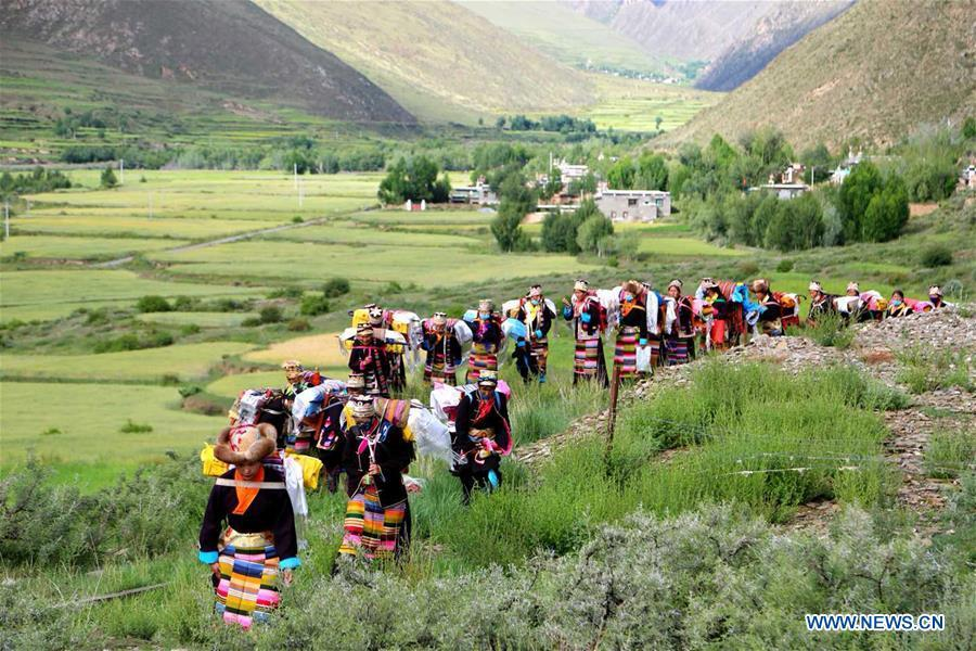 People of Tibetan ethnic group take part in a ceremony to pray for harvest during the annual Ongkor Festival in Qangkyim Village of Shannan City, southwest China\'s Tibet Autonomous Region, July 14, 2018. The Ongkor Festival, or Bumper Harvest Festival, which has a history of more than 1,500 years, is celebrated annually by local farmers praying for good harvests of crops. (Xinhua/Lhunzhub Cering)