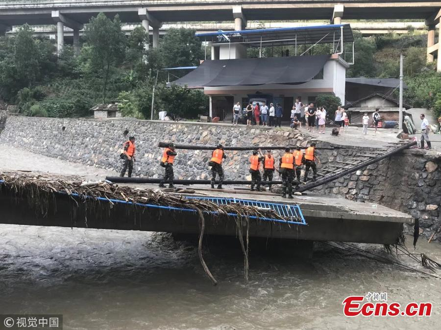 Rescuers help people affected by heavy rain and floods in Lueyang County, Northwest China's Shaanxi Province. Six hours of heavy rain on July 13 and 14 caused landslides in the county, cutting off power and telecommunication and transportation links in many areas, and causing a direct economic loss of 193 million yuan ($28.8 million). Hundreds of firefighters and police officers, including armed police, have joined search and rescue efforts. Some police officers had to walk on foot for 57 kilometers. (Photo/VCG)