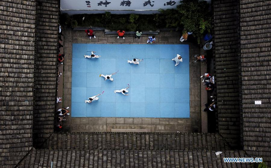 Aerial photo taken on July 14, 2018 shows a martial arts instructor demonstrating actions for children at Wenzhou Wushu Museum in Wenzhou, east China\'s Zhejiang Province. More than 120 children visited the museum on Sunday to learn about martial arts. (Xinhua/Su Qiaojiang)