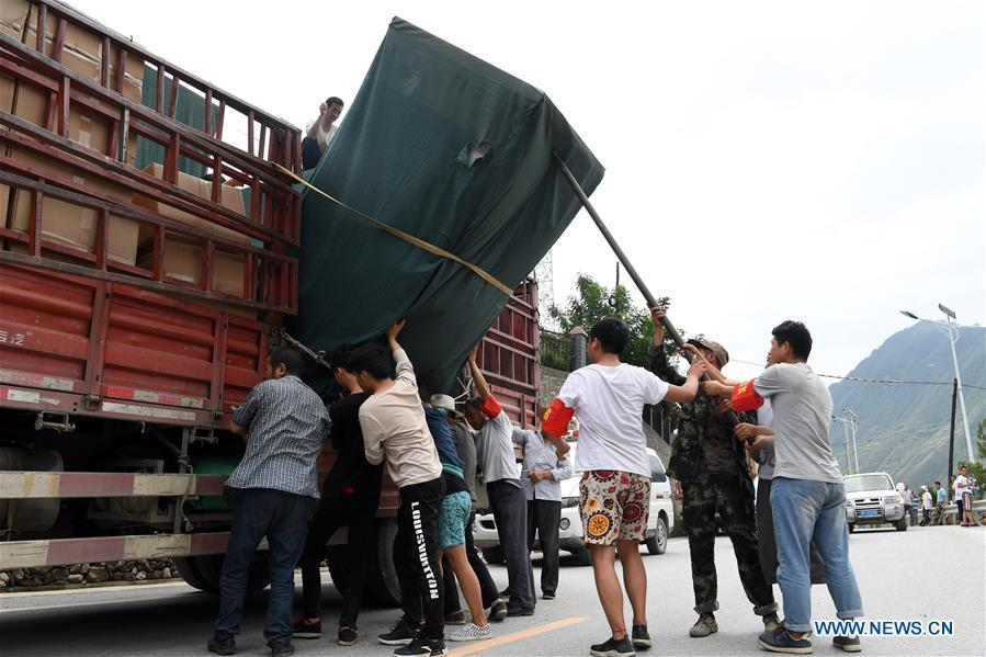 Villagers unload relief supplies for flood victims in Nanyu Town of Zhouqu County, northwest China\'s Gansu Province, July 15, 2018. Emergency relief supplies have been sent to severely flooded areas in Zhouqu County and rescue work has been carried out here. Heavy rainstorms triggered a landslide Thursday in Zhouqu County, but no casualties have been reported. (Xinhua/Fan Peishen)