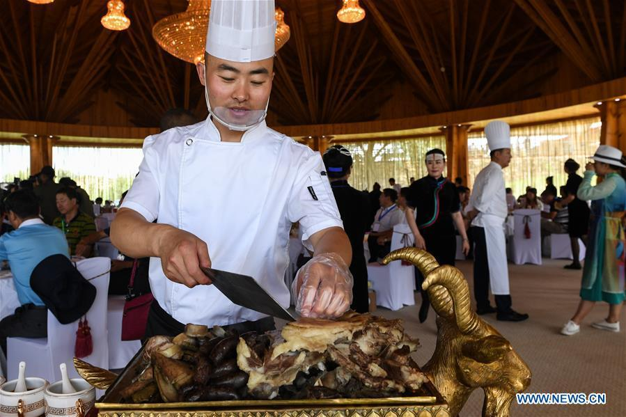 A chef demonstrates how to cut hand-served mutton at a ceremony in Xilin Gol, north China\'s Inner Mongolia Autonomous Region, July 15, 2018. To better inherit and develop Mongolian food and promote tourism of Inner Mongolia, the Tourism Development Board of Inner Mongolia and Xilin Gol Meng jointly released a list of eight unique Mongolian dishes on Sunday. (Xinhua/Liu Lei)