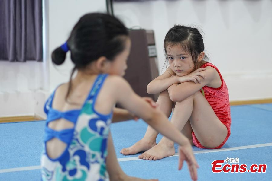 Zhang Renchi watches as a student massages herself during a break in training at the Amateur Children\'s Gymnastics Training School in Rongjiang County, Southwest China's Guizhou Province, July 16, 2018. There are 60 children taking part in gymnastics training at the school during their spare time. Since 1972, the county has sent 21 athletes to the provincial gymnastics and gymnastics trampoline teams, among whom six later became national team members. The county is home to Liu Rongbing, who won a gold medal for the men\'s team in the 2014 World Artistic Gymnastics Championships. (Photo: China News Service/He Junyi)