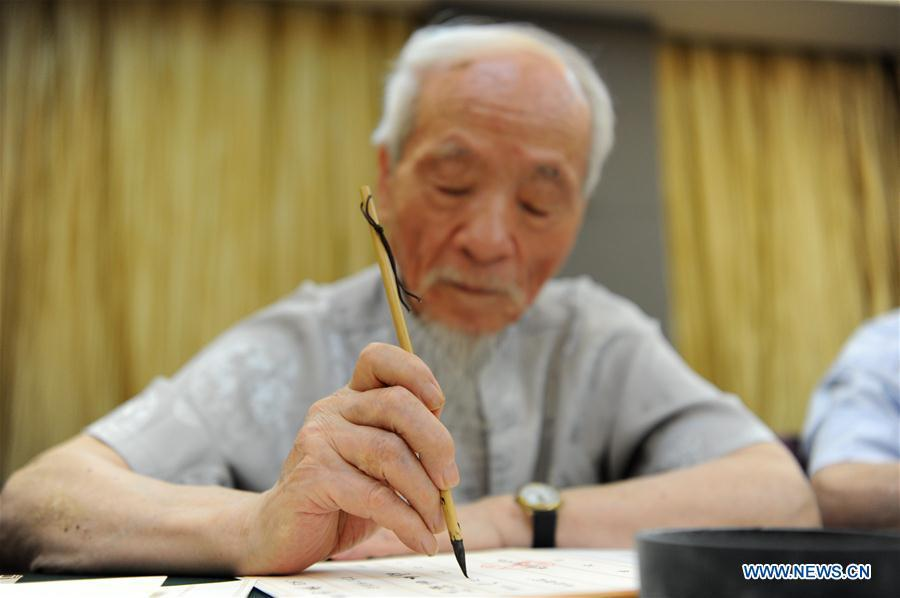Wu Yaohui, a retired teacher from Shaanxi Normal University, writes an admission letter with Chinese writing brush in Xi\'an, northwest China\'s Shaanxi Province, July 16, 2018. Around 4,500 admission letters written by representatives of alumni and retired teachers from Shaanxi Normal University will be delivered to freshmen. The hand-written admission letter has become a feature of Shaanxi Normal University since 2007. (Xinhua/Zhang Bowen)