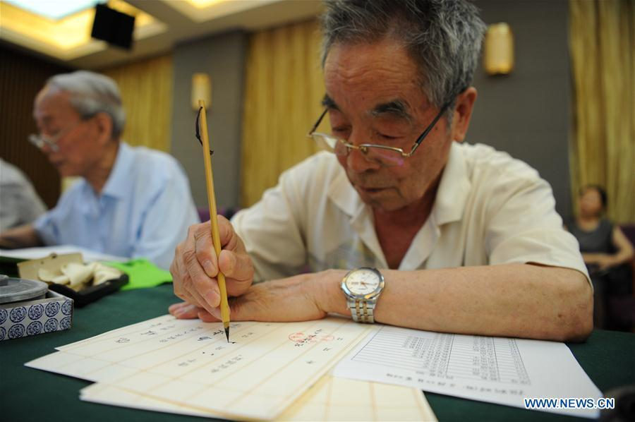 Yang Mingtang, a retired teacher from Shaanxi Normal University, writes an admission letter with Chinese writing brush in Xi\'an, northwest China\'s Shaanxi Province, July 16, 2018. Around 4,500 admission letters written by representatives of alumni and retired teachers from Shaanxi Normal University will be delivered to freshmen. The hand-written admission letter has become a feature of Shaanxi Normal University since 2007. (Xinhua/Zhang Bowen)