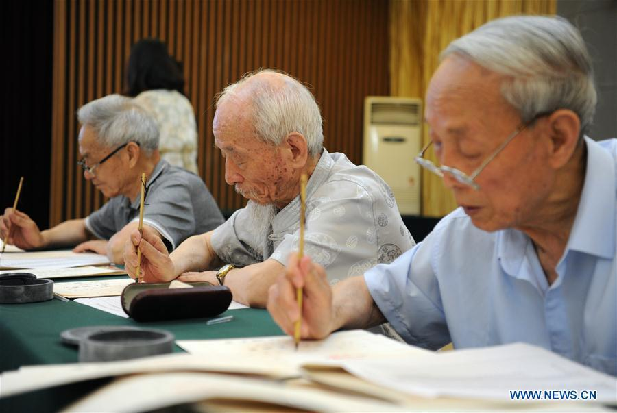Wu Yaohui (2nd R), a retired teacher from Shaanxi Normal University, writes an admission letter with Chinese writing brush in Xi\'an, northwest China\'s Shaanxi Province, July 16, 2018. Around 4,500 admission letters written by representatives of alumni and retired teachers from Shaanxi Normal University will be delivered to freshmen. The hand-written admission letter has become a feature of Shaanxi Normal University since 2007. (Xinhua/Zhang Bowen)