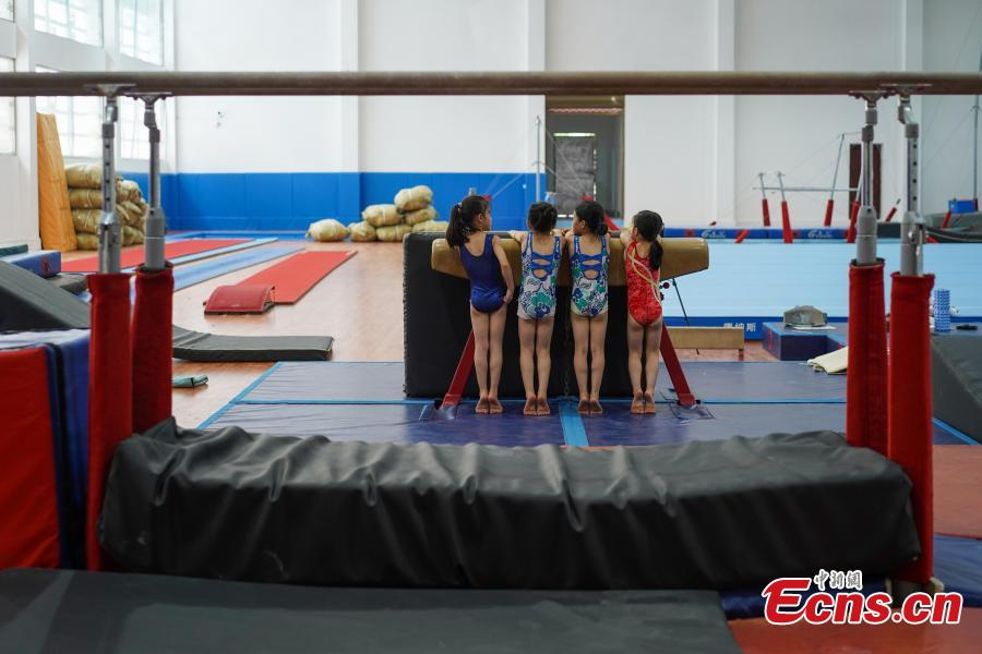 Students train at the Amateur Children\'s Gymnastics Training School in Rongjiang County, Southwest China's Guizhou Province, July 16, 2018. There are 60 children taking part in gymnastics training at the school during their spare time. Since 1972, the county has sent 21 athletes to the provincial gymnastics and gymnastics trampoline teams, among whom six later became national team members. The county is home to Liu Rongbing, who won a gold medal for the men\'s team in the 2014 World Artistic Gymnastics Championships. (Photo: China News Service/He Junyi)