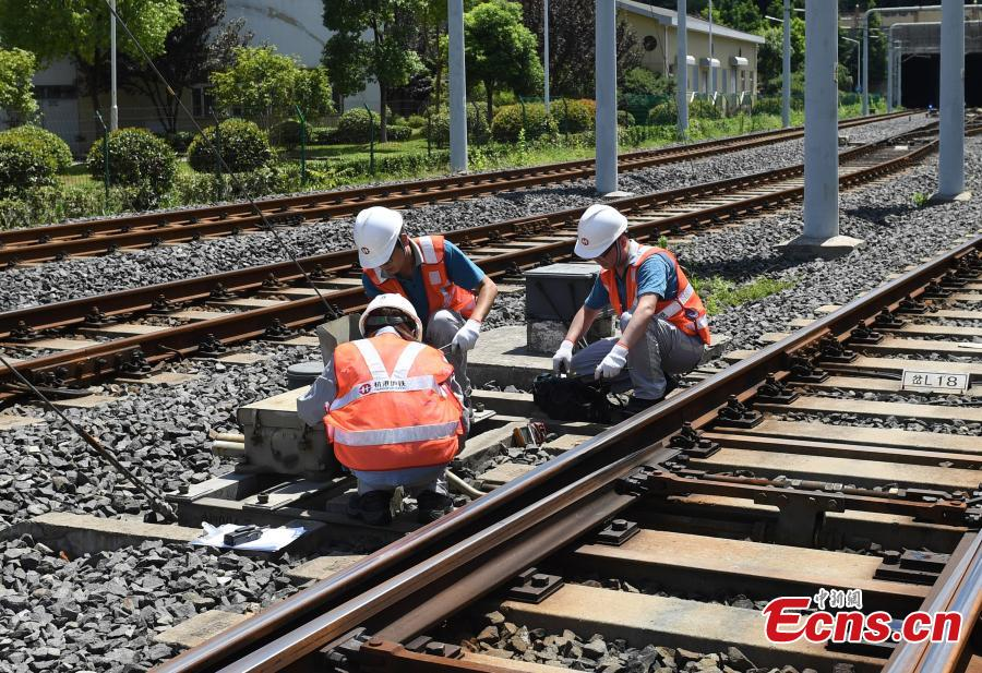 Technicians work on a railway track as temperatures reach a high of 36 degrees centigrade in Hangzhou City, East China's Zhejiang Province, July 16, 2018. (Photo: China News Service/Wang Gang)