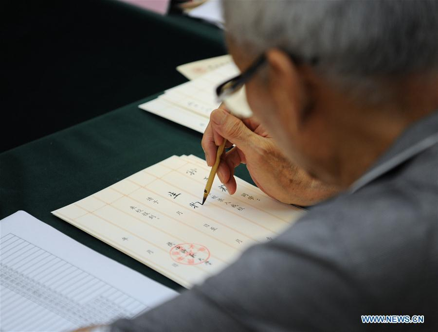 Qu Peiheng, a retired teacher from Shaanxi Normal University, writes an admission letter with Chinese writing brush in Xi\'an, northwest China\'s Shaanxi Province, July 16, 2018. Around 4,500 admission letters written by representatives of alumni and retired teachers from Shaanxi Normal University will be delivered to freshmen. The hand-written admission letter has become a feature of Shaanxi Normal University since 2007. (Xinhua/Zhang Bowen)