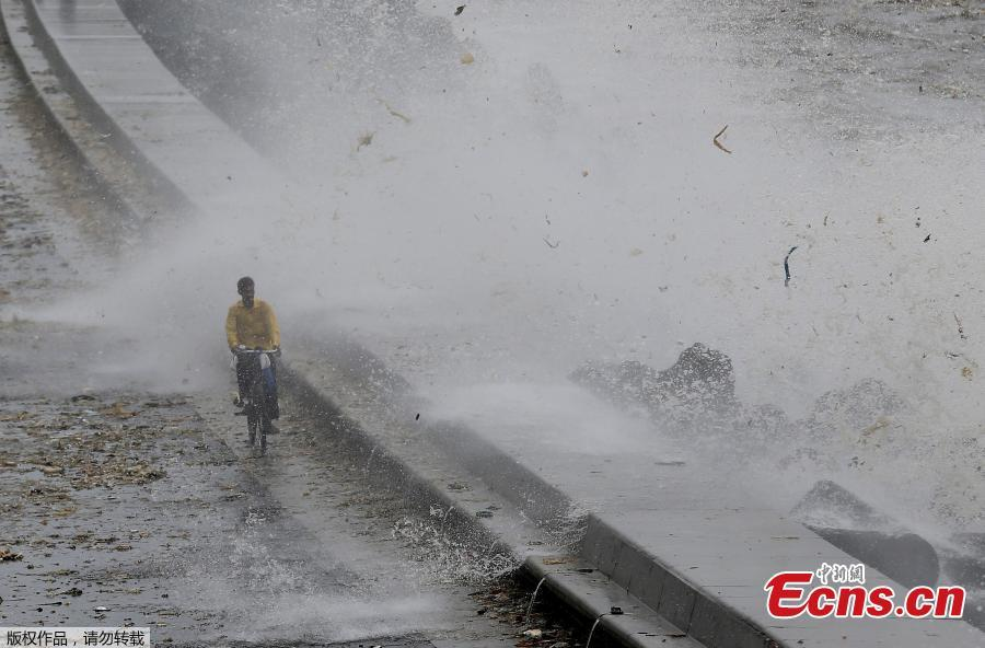 A man walks as a wave crashes during high tide at a sea front in Mumbai, India, July 13, 2018. (Photo/Agencies)