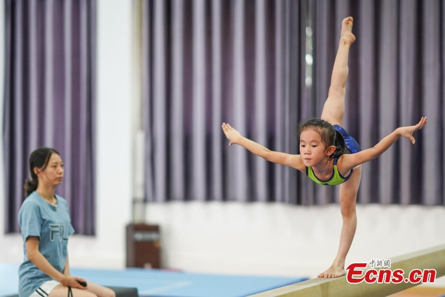 Zhang Han (R) trains at the Amateur Children\'s Gymnastics Training School in Rongjiang County, Southwest China's Guizhou Province, July 16, 2018. There are 60 children taking part in gymnastics training at the school during their spare time. Since 1972, the county has sent 21 athletes to the provincial gymnastics and gymnastics trampoline teams, among whom six later became national team members. The county is home to Liu Rongbing, who won a gold medal for the men\'s team in the 2014 World Artistic Gymnastics Championships. (Photo: China News Service/He Junyi)