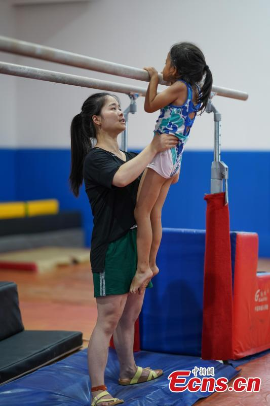 Instructor Zuo Ling trains a student at the Amateur Children\'s Gymnastics Training School in Rongjiang County, Southwest China's Guizhou Province, July 16, 2018. There are 60 children taking part in gymnastics training at the school during their spare time. Since 1972, the county has sent 21 athletes to the provincial gymnastics and gymnastics trampoline teams, among whom six later became national team members. The county is home to Liu Rongbing, who won a gold medal for the men\'s team in the 2014 World Artistic Gymnastics Championships. (Photo: China News Service/He Junyi)