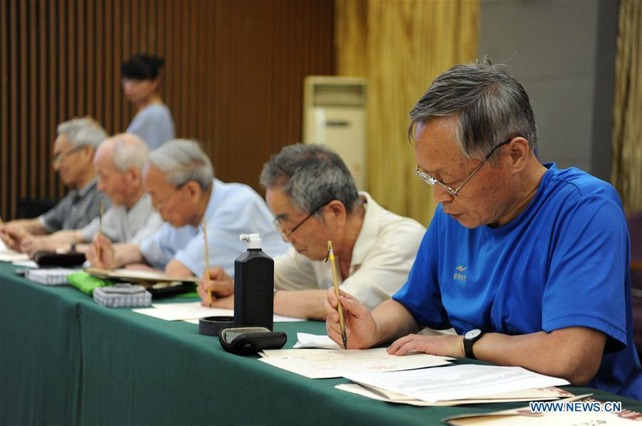 Ma Fantao (1st R), a retired teacher from Shaanxi Normal University, writes an admission letter with Chinese writing brush in Xi\'an, northwest China\'s Shaanxi Province, July 16, 2018. Around 4,500 admission letters written by representatives of alumni and retired teachers from Shaanxi Normal University will be delivered to freshmen. The hand-written admission letter has become a feature of Shaanxi Normal University since 2007. (Xinhua/Zhang Bowen)