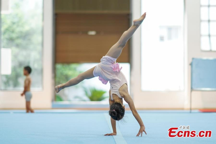 A girl trains at the Amateur Children\'s Gymnastics Training School in Rongjiang County, Southwest China's Guizhou Province, July 16, 2018. There are 60 children taking part in gymnastics training at the school during their spare time. Since 1972, the county has sent 21 athletes to the provincial gymnastics and gymnastics trampoline teams, among whom six later became national team members. The county is home to Liu Rongbing, who won a gold medal for the men\'s team in the 2014 World Artistic Gymnastics Championships. (Photo: China News Service/He Junyi)