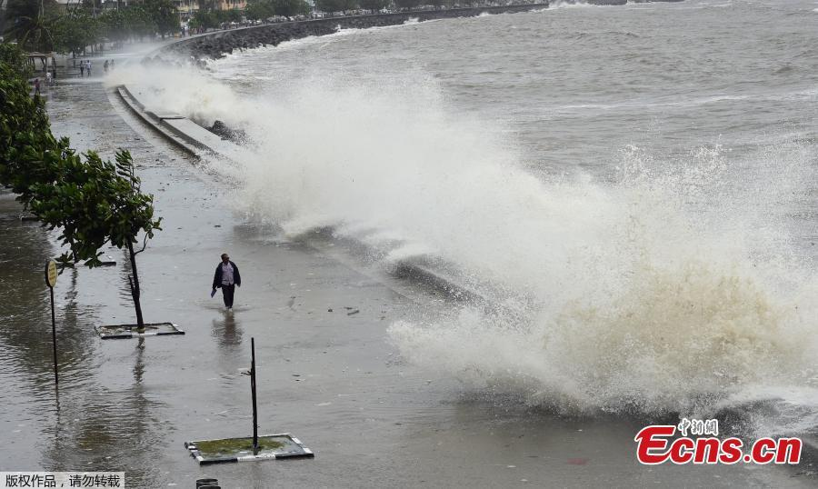 A man rides his bicycle as a wave crashes during high tide at a sea front in Mumbai, India, July 13, 2018. (Photo/Agencies)