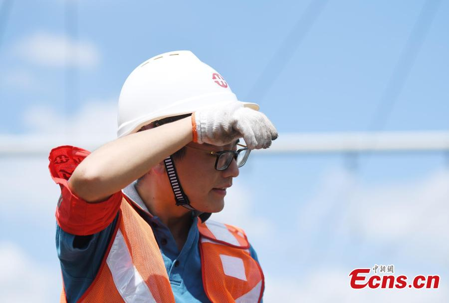 A signal inspection technician works on a railway track as temperatures reach a high of 36 degrees centigrade in Hangzhou City, East China's Zhejiang Province, July 16, 2018. (Photo: China News Service/Wang Gang)