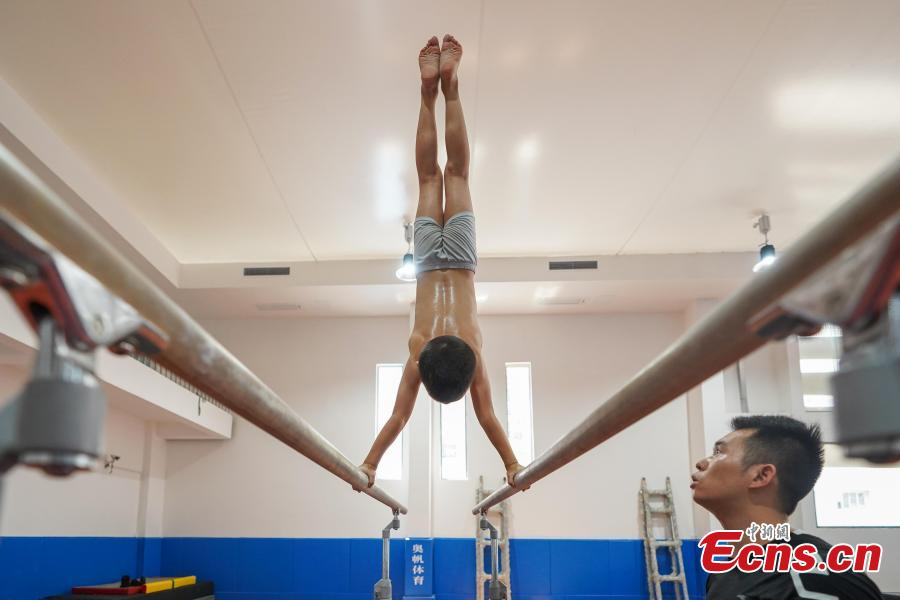 Instructor Liu Shiya trains student Ye Zhansong at the Amateur Children\'s Gymnastics Training School in Rongjiang County, Southwest China's Guizhou Province, July 16, 2018. There are 60 children taking part in gymnastics training at the school during their spare time. Since 1972, the county has sent 21 athletes to the provincial gymnastics and gymnastics trampoline teams, among whom six later became national team members. The county is home to Liu Rongbing, who won a gold medal for the men\'s team in the 2014 World Artistic Gymnastics Championships. (Photo: China News Service/He Junyi)