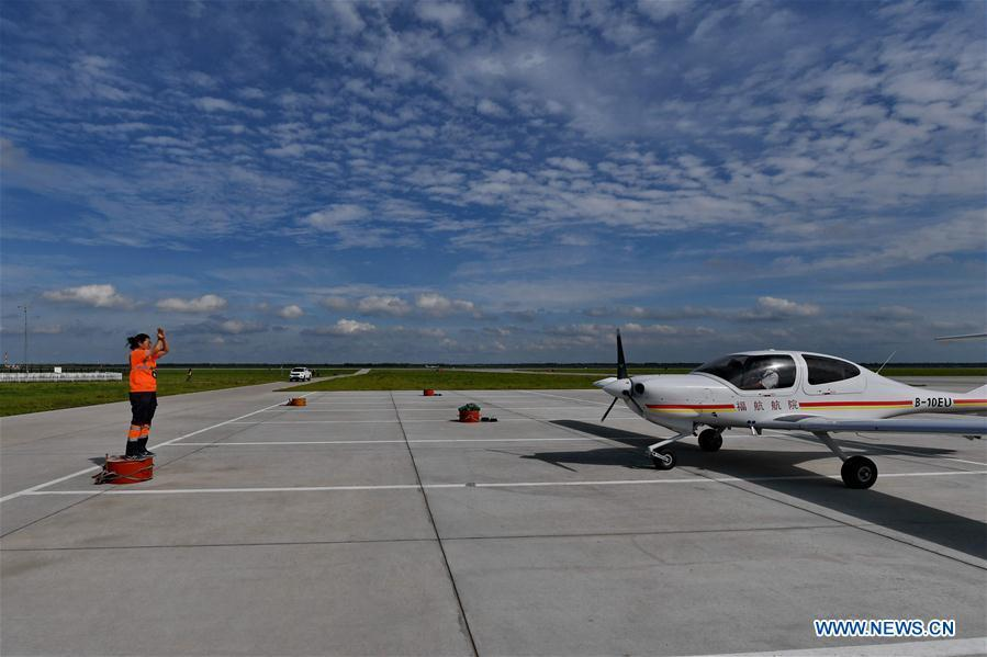 Deng Yun guides an aircraft to a specific place at the Chagan Lake airport in Songyuan, northeast China\'s Jilin Province, July 17, 2018. Deng was born in 1991. She is an aircraft maintenance technician of an aviation academy in Jilin. The young female engineer and other nine colleagues are in charge of training plane maintenance at the airport. To ensure the flight safety, they need to check more than 100 items before a plane takes off. (Xinhua/Zhang Nan)