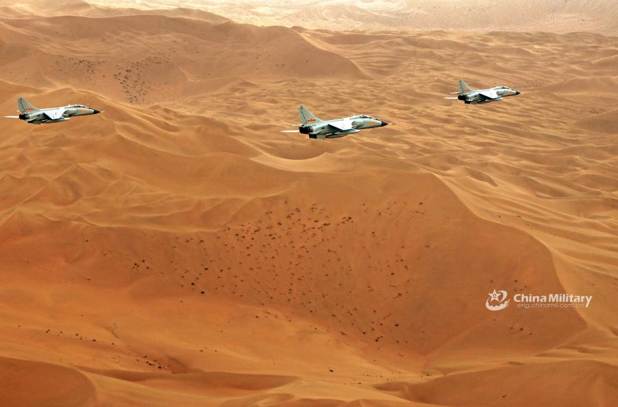 Three fighter jets conduct a fly-by over the desert during the \