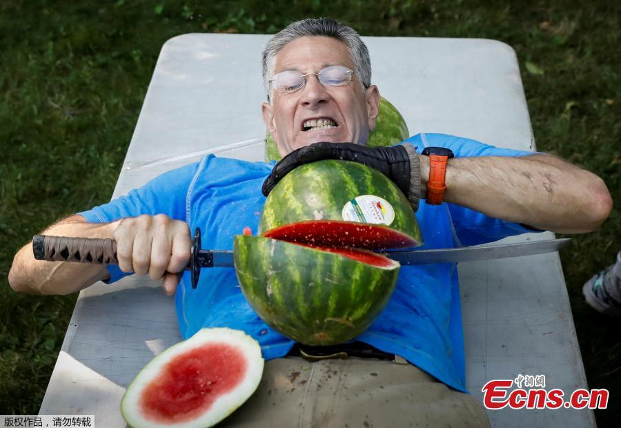Ashrita Furman, who holds more Guinness World Records than anyone, attempts to set a new record for slicing the most watermelons in half on his own stomach in one minute in New York City, U.S., July 17, 2018. (Photo/Agencies)