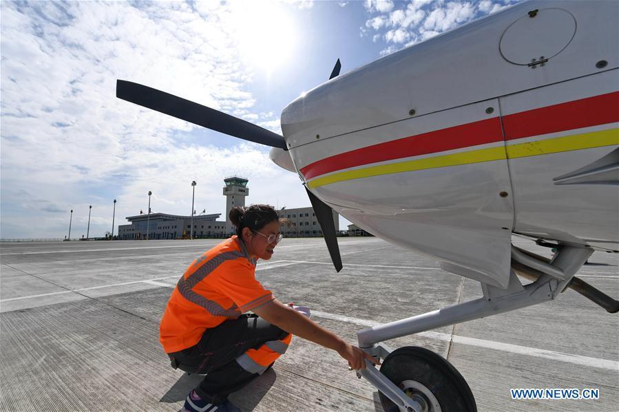 Deng Yun checks undercarriage of an aircraft at the Chagan Lake airport in Songyuan, northeast China\'s Jilin Province, July 17, 2018. Deng was born in 1991. She is an aircraft maintenance technician of an aviation academy in Jilin. The young female engineer and other nine colleagues are in charge of training plane maintenance at the airport. To ensure the flight safety, they need to check more than 100 items before a plane takes off. (Xinhua/Zhang Nan)