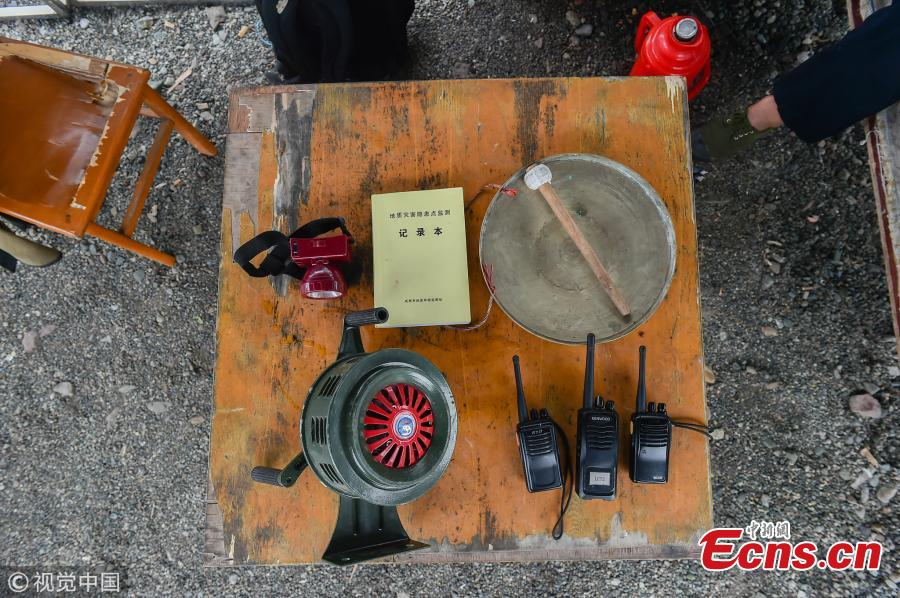 Mou Huaiqing, 65, shows his work equipment including a flashlight and an alarm apparatus in Dujiangyan City, Southwest China's Sichuan Province. For the past nine years, since the deadly May 12 earthquake in 2008, Mou and his colleagues have been responsible for 24-hour monitoring of the valley from May to October for signs of potential landslides that could pose a threat to local villagers. They check for any cracks on mountain slopes, for example. Mou helped evacuate 300 residents and tourists in a timely manner as he sounded an alarm to warn of a landslide in August 2010. The team has sounded warnings for a dozen geological hazards. (Photo/VCG)