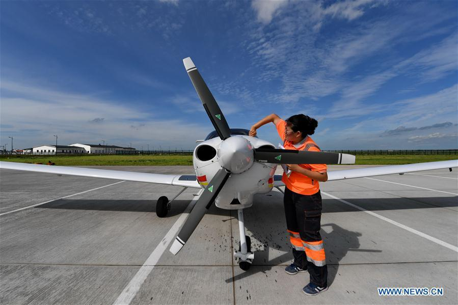 Deng Yun checks an aircraft at the Chagan Lake airport in Songyuan, northeast China\'s Jilin Province, July 17, 2018. Deng was born in 1991. She is an aircraft maintenance technician of an aviation academy in Jilin. The young female engineer and other nine colleagues are in charge of training plane maintenance at the airport. To ensure the flight safety, they need to check more than 100 items before a plane takes off. (Xinhua/Zhang Nan)