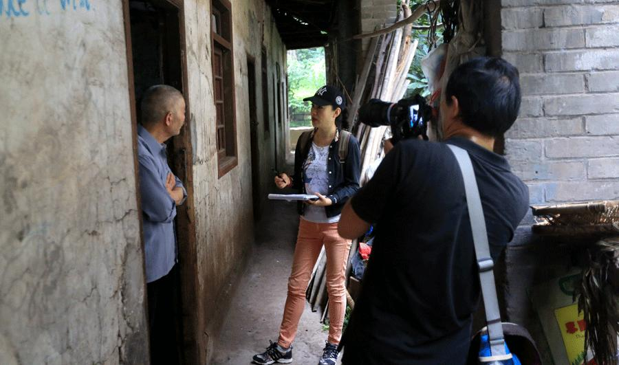 Volunteers from Chongqing interview residents in old houses for a cultural heritage protection project. (Photo provided to China Daily)