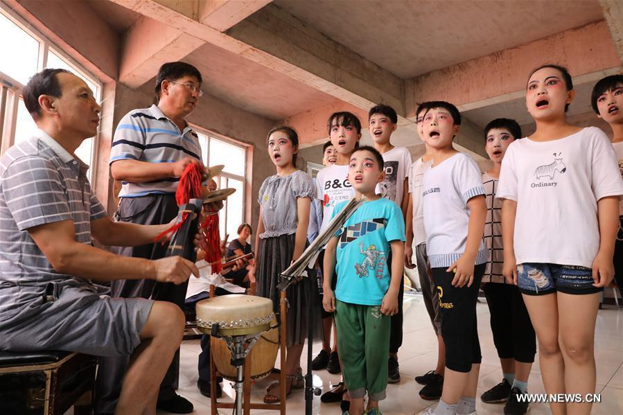 Students from a primary school learn opera under the guidance of teachers in Shijiazhuang, north China\'s Hebei Province, July 18, 2018. Chinese students have entered their summer vacation, during which many of them chose to spend the vacation by developing their hobbies. (Xinhua/Liang Zidong)