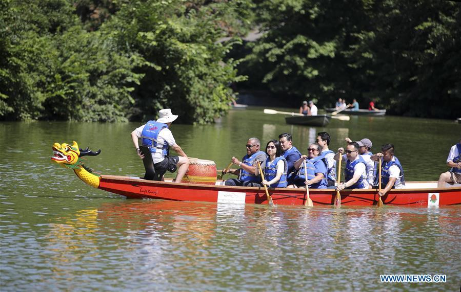 Invited guests row a dragon boat prior to a traditional dragon boat awakening ceremony for the 28th annual Hong Kong Dragon Boat Festival in New York, the United States, on July 18, 2018. The ceremony marked the start of the training period for over 200 teams competing in this year\'s dragon boat races on Aug. 11 and Aug. 12 in New York. (Xinhua/Wang Ying)