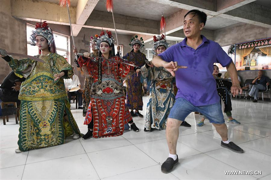Students from a primary school learn opera movements under the guidance of a teacher in Shijiazhuang, north China\'s Hebei Province, July 18, 2018. Chinese students have entered their summer vacation, during which many of them chose to spend the vacation by developing their hobbies. (Xinhua/Chen Qibao)