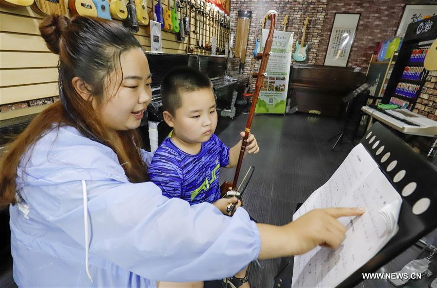 A student learns to play erhu, a Chinese two-stringed musical instrument, under the guidance of his teacher in Zunhua City, north China\'s Hebei Province, July 18, 2018. Chinese students have entered their summer vacation, during which many of them chose to spend the vacation by developing their hobbies. (Xinhua/Liu Mancang)