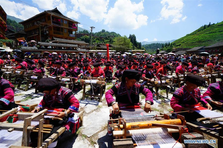 Women of Yao ethnic group present the skills of making folk costumes in Longji Township of Guilin, south China\'s Guangxi Zhuang Autonomous Region, July 18, 2018. Local people of Yao ethnic group on Wednesday celebrated annual \